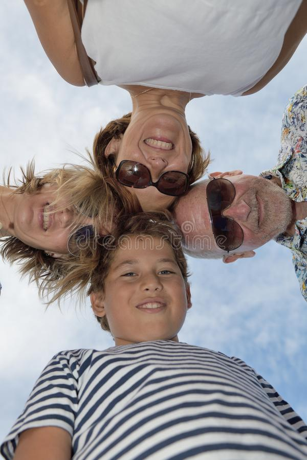 View from happy below four people with heads together royalty free stock image