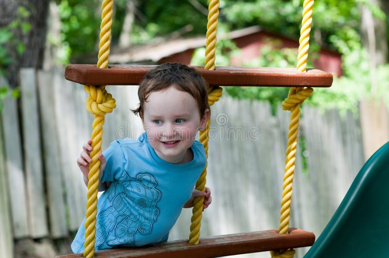 Happy little child boy climbing on the rope ladder outside stock photography