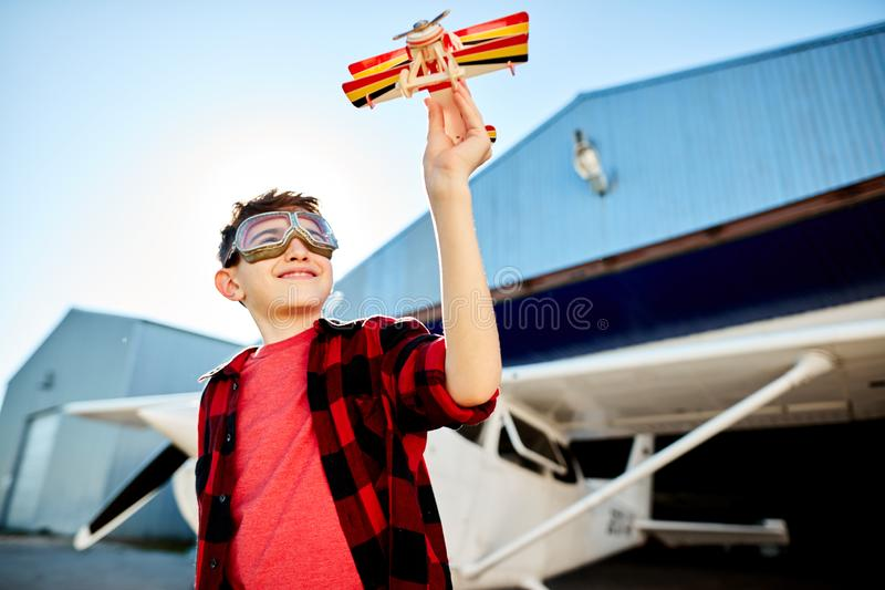 Happy kid playing with toy airplane near hangar, dreams to be a pilot. View of happy smiling kid with toy airplane, dreams to be a pilot, playing outdoor near royalty free stock images