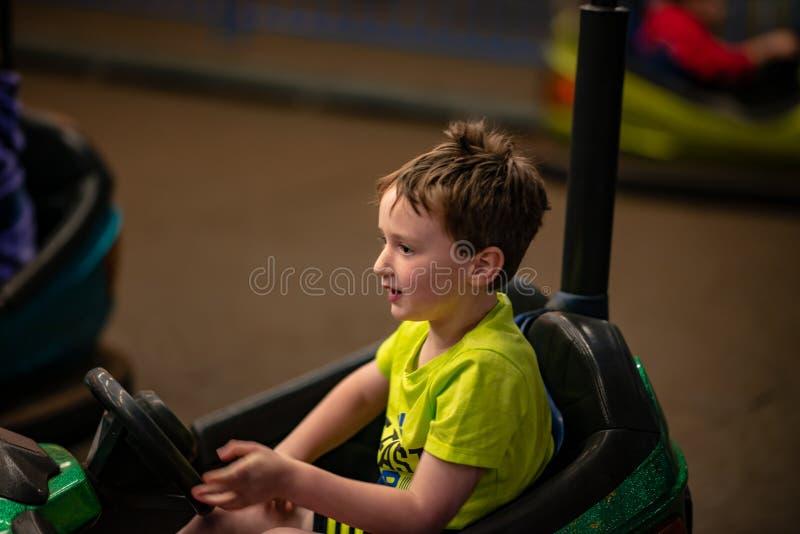 Happy young boy rides electric bumper car amusement ride on shore boardwalk stock images
