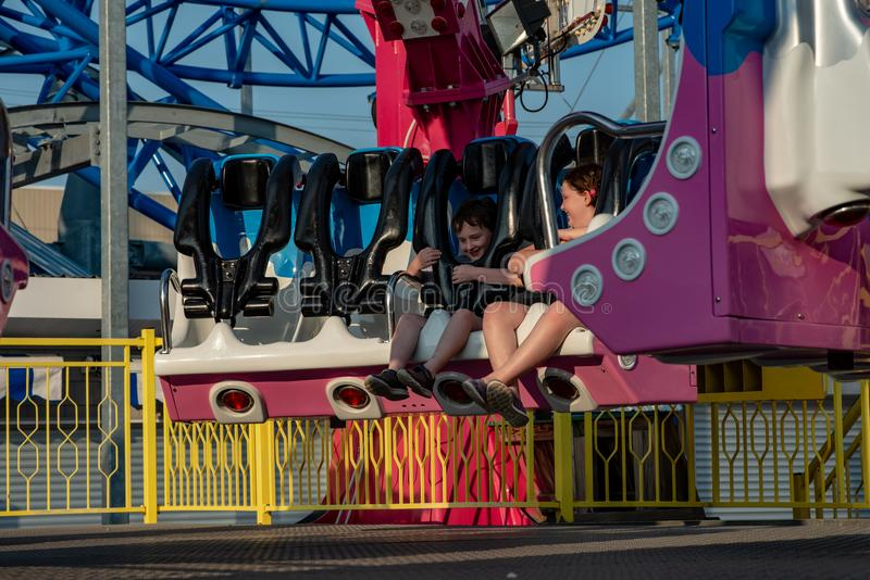 Happy young brother and sister having fun on boardwalk amusement ride royalty free stock photos