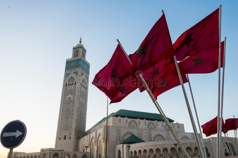 View of Hassan II mosque and a waving moroccan flags. Against sky - Casablanca - Morocco stock images
