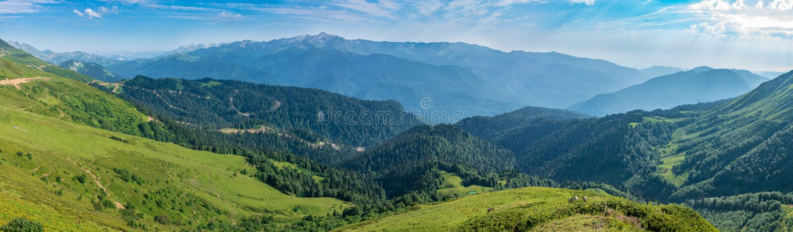 The view from the height of the green mountain valley with a cable car, surrounded by high mountains. Snow-capped mountain peaks. On the horizon. Krasnaya royalty free stock photos