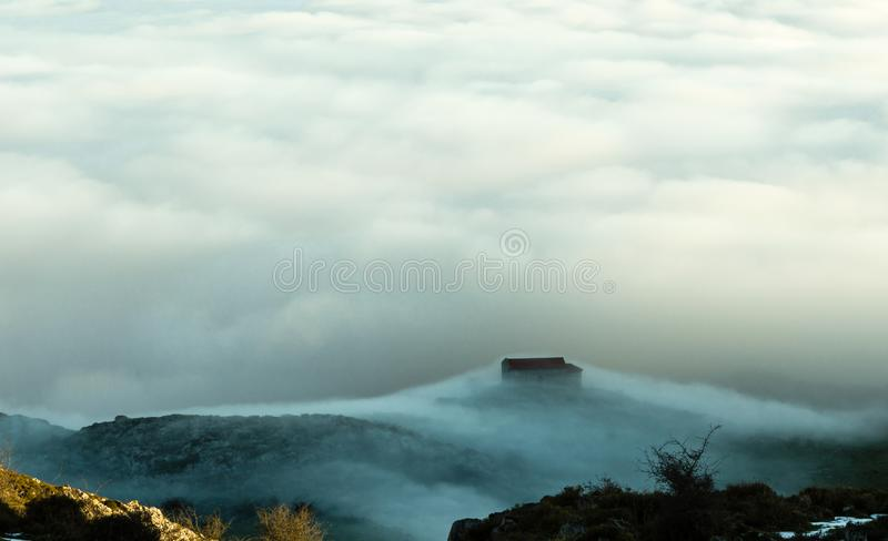 View of the hermitage of La Magdalena, on mountain Mount Monsacro, at dawn. With a sea clouds of background. Asturias, Spain royalty free stock images