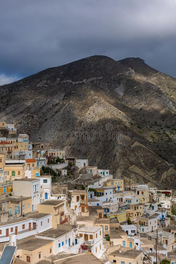 View of a high rocky mountain surrounded by white modern buildings under a cloudy sky in Greece. A view of a high rocky mountain surrounded by white modern stock images