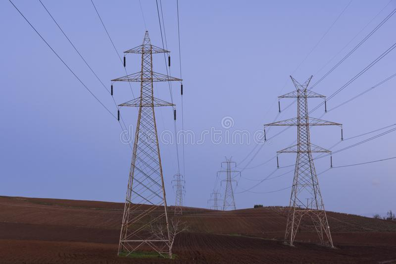 View of high voltage pylons run through fields with arable land. At Boeotia, central Greece royalty free stock photography