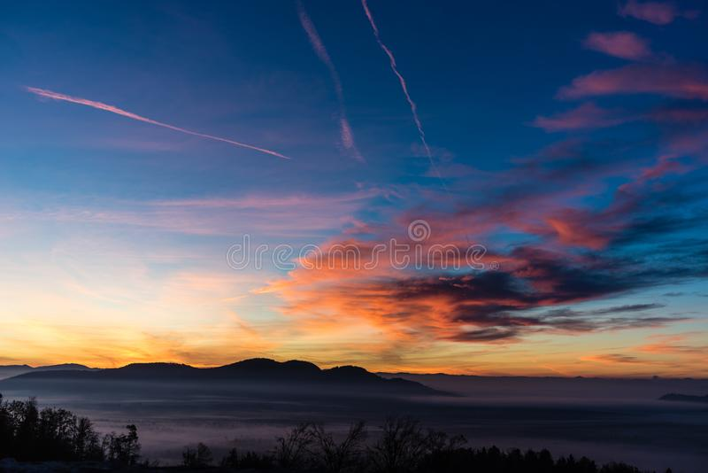 View from a hill of a beautiful evening nature. Red glowing sky with clouds and mist covered valley with mountains in background stock photography