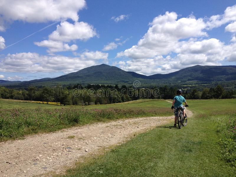 Boy enjoys the view on a bike ride. A boy enjoys the view of Burke Mountain on top of a hill in Vermont stock image
