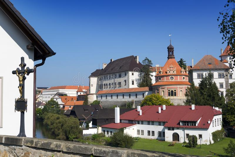 View from the hill with a crucifix inscription in Czech- with Christ the world will be saved on renaissance style castle, 16th c. View from the hill with a royalty free stock photo