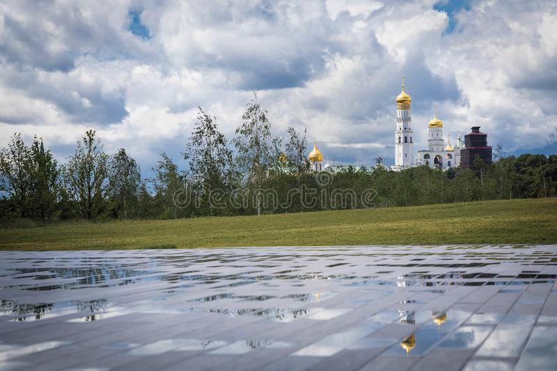 View from the hill of the Zaryadye park on church Ivan the Great Bell Tower and reflections. Cloudy weather with thunderclouds on. View from the hill of the royalty free stock images