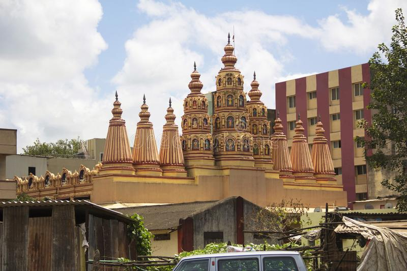 View of Hindu temple gopuram or towers with buildings and sky in background, Pune stock photography