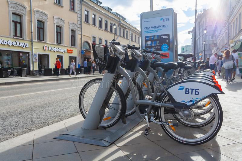 View on a hire bikes on a docking station on the city street. Moscow, Russia, August 2018: View on a hire bikes on a docking station on the city street editorial royalty free stock photography