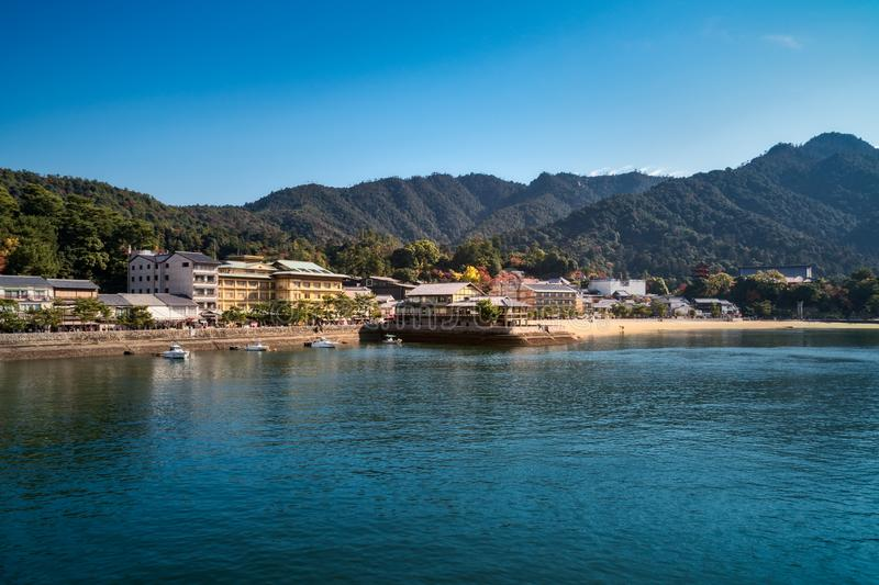 View from Hiroshima Bay of the coast of Miyajima Island in autumn. View from the bay of the coast of Miyajima Island in autumn with Itsukushima Shrine and Mount royalty free stock image