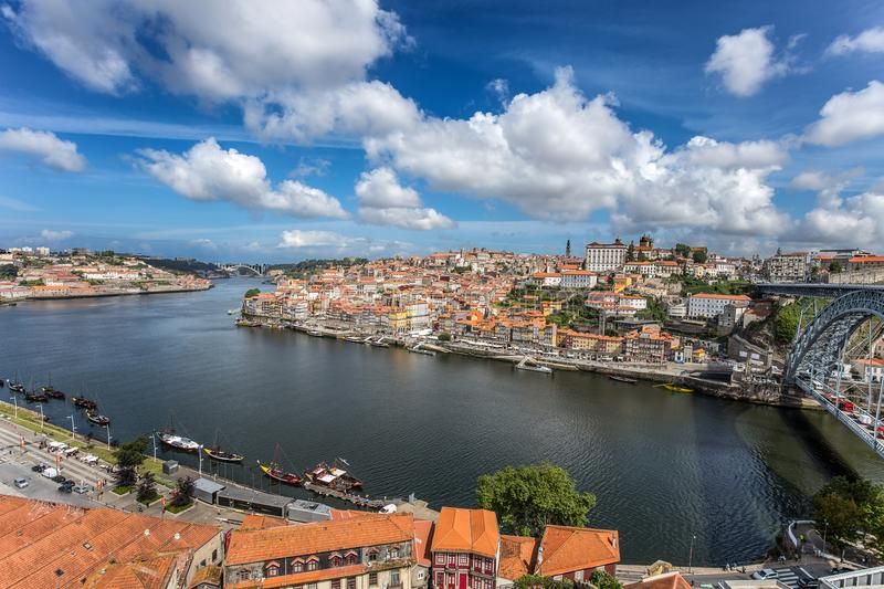 View of the historic city of Porto, Portugal with the Dom Luiz bridge. across the Douro river and the traditional rabelo boats. royalty free stock images
