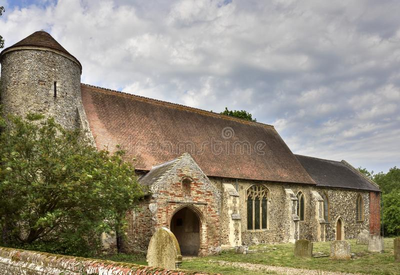 Historic Round Tower Church of East England. View of the historic round tower church and graveyard of St. Mary, Moulton, Beighton, Broadland, Norfolk, England stock photography