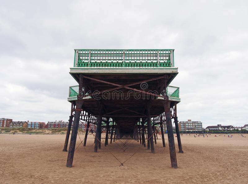 View of the historic victorian pier at saint annes on sea in in lancashire with the beach at low tide and buildings along the shor. Front view of the historic stock photos