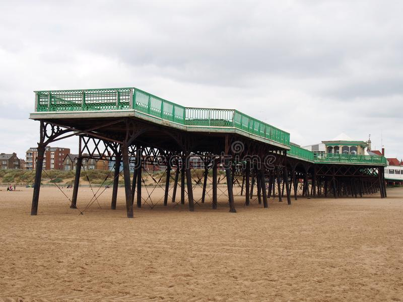 View of the historic victorian pier at saint annes on sea in in lancashire with the beach at low tide and buildings along the shor. A view of the historic stock photo