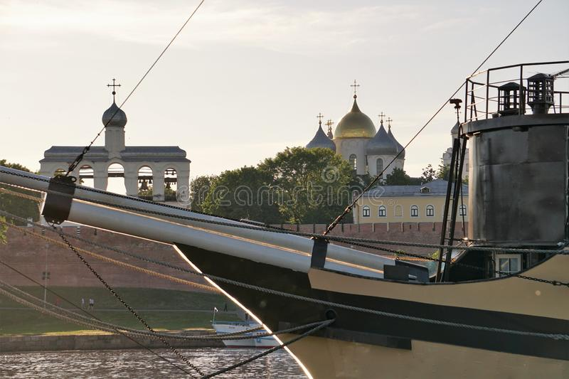 View of the historical buildings in the Novgorod Kremlin through the bowsprit of the ship-restaurant on the Volkhov River. royalty free stock image
