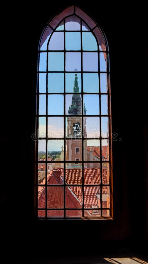 View on Holy Spirit Church and historical buildings through the stained glass window of Old Town Hall in Torun, Poland. August royalty free stock image