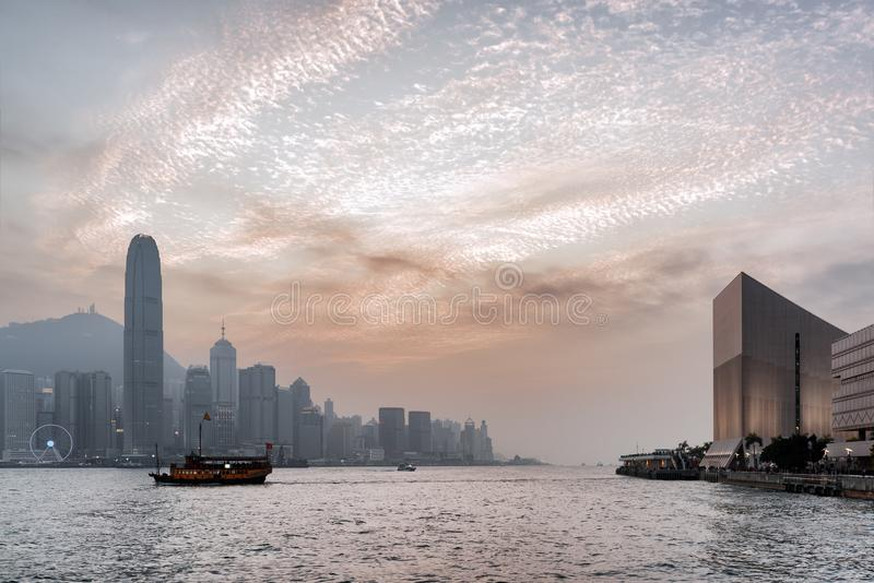 View of Hong Kong city and a ship in Victoria harbor with beautiful glowing clouds in the sky at sunset. Hong Kong is popular tourist destination of Asia and stock photo
