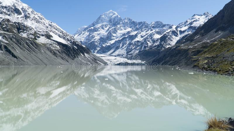 View of lake with the highest peak of New Zealand Mt. Cook in background. View of blue lake with the highest peak of New Zealand Mt. Cook in background stock photo