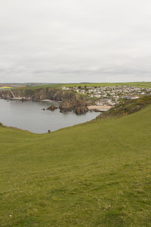 View of Hope Cove, Devon from the Bolt tail headland. Grass hill going down in the foreground. Hope cove bay in portrait shape picture stock photo