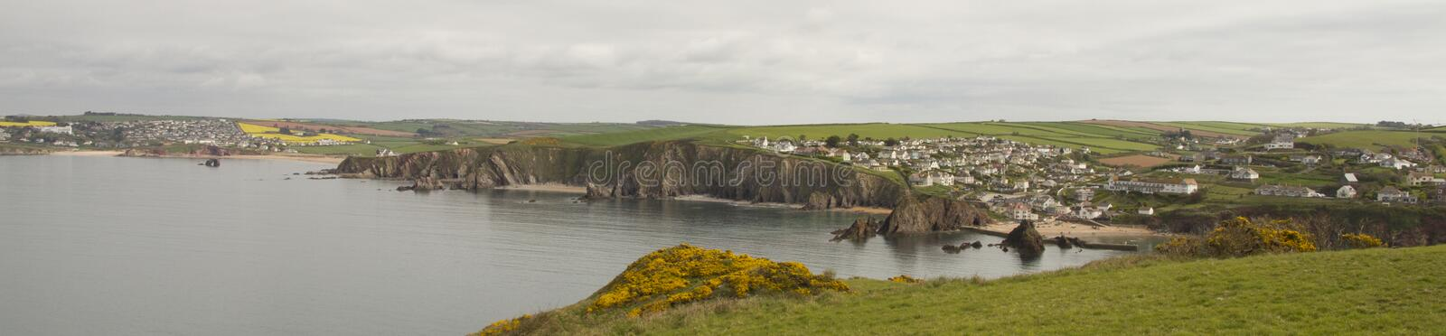 View of Hope Cove, Devon from the Bolt tail headland. Yellow heather in the foreground. Hope cove bay and Thurlestone bay in background stock photos