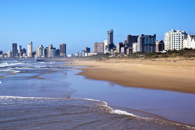 View of Hotels from Shoreline in Durban South Africa. DURBAN, SOUTH AFRICA - DECEMBER 4, 2014 : Early morning people on beach against Golden Mile Beach Front royalty free stock image