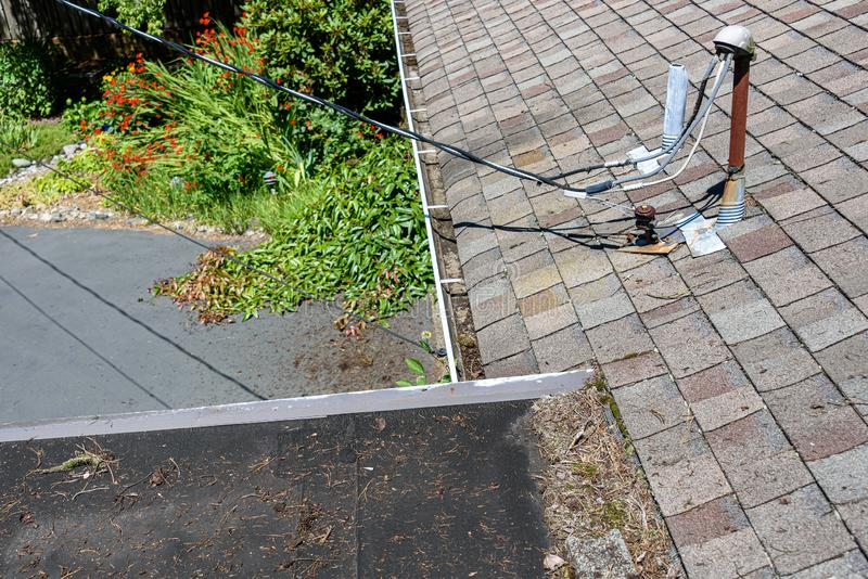View from house rooftop of roof shingles, gutters, tree debris, moss, utility lines, driveway and garden stock photos