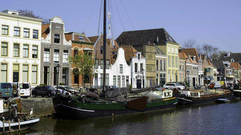 A view on houseboats, barges in a canal and old houses with facades royalty free stock photography
