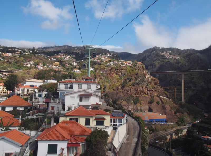 view of the of houses and market gardens of funchal from the cable car running up the mountain to monte with road bridge and stock photos