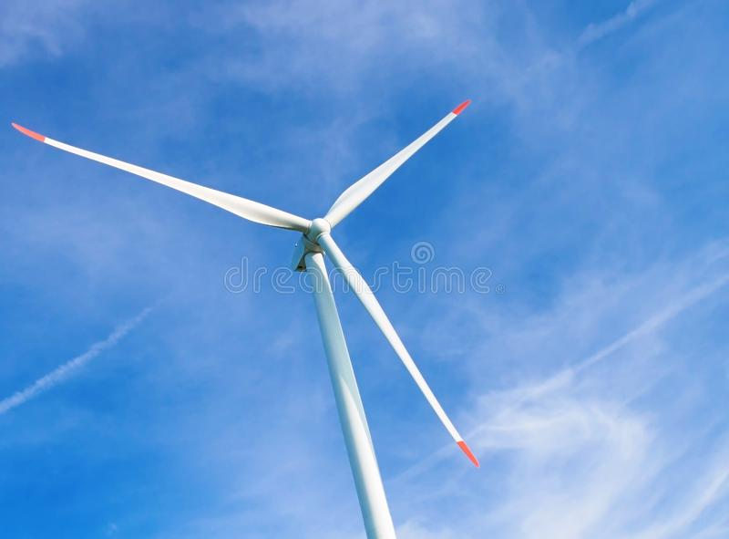 View on huge white wind generator on blue sky and white clouds background. Nature friendly wind energy industrial technology. Wind. Mill in Europe royalty free stock image