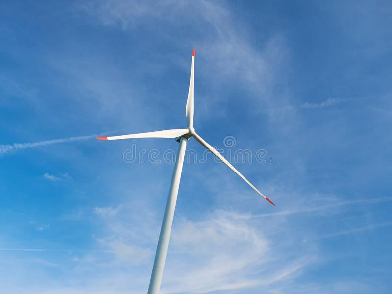 View on huge white wind generator on blue sky and white clouds background. Nature friendly wind energy technology. Windmill in Eur. Ope stock images