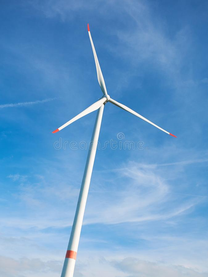 View on huge white wind generator on blue sky and white clouds background. Nature friendly wind energy technology. Windmill in Eur. Ope royalty free stock photo