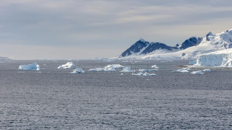 View of ice mountains and icebergs on bay in Antarctica stock images