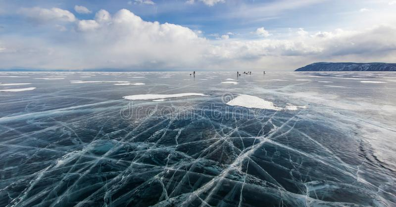 view of ice water surface under cloudy sky during daytime and group of hikers on background , russia, lake stock photos