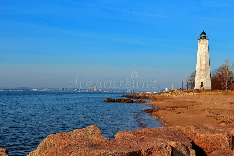 Looking at an Iconic Lighthouse in New England in the Winter. View of an Iconic New England Lighthouse in Winter with a calm ocean and a rocky shore royalty free stock photography