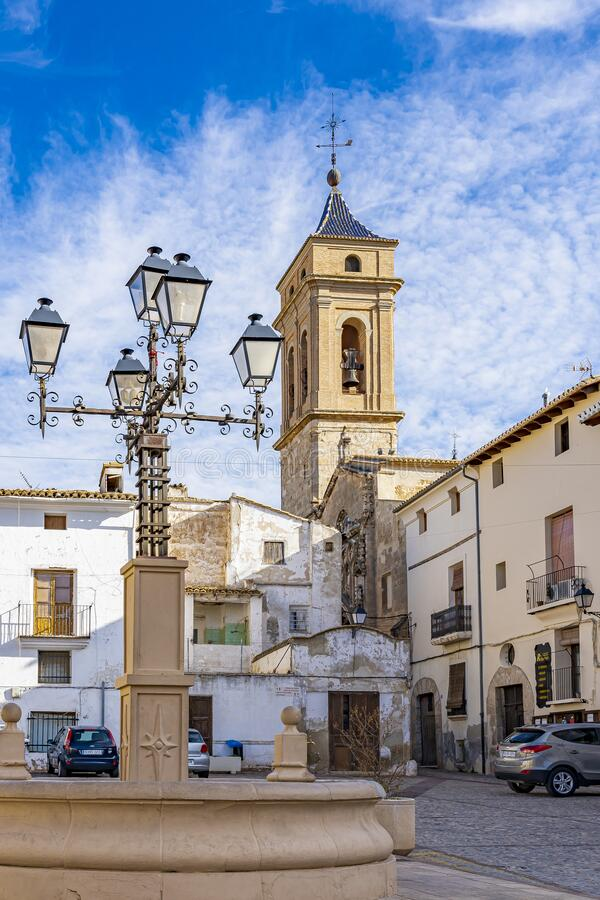 View of Iglesia del Salvador from behind the fountain with beautiful lantern on the Plaza de Albornoz Square in Requena, Spain stock photo