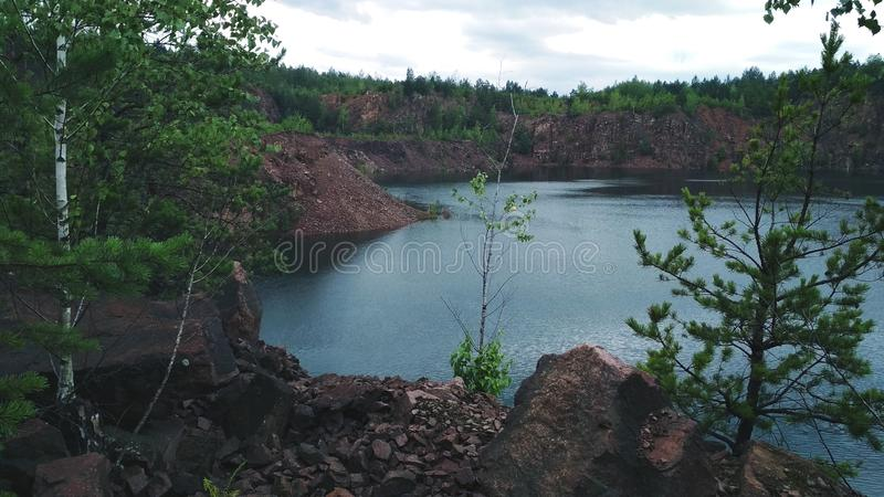 View on inactive abandoned granite quarry with beautiful blue water. View on inactive abandoned granite quarry with beautiful blue water royalty free stock photos