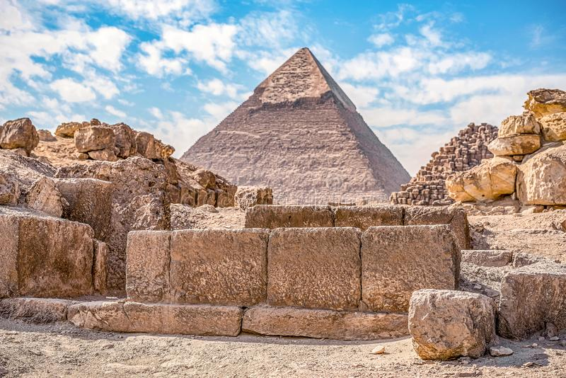 View of the incredibly majestic pyramid of the cheops on a sunny day in the desert with ancient ruins stock photo