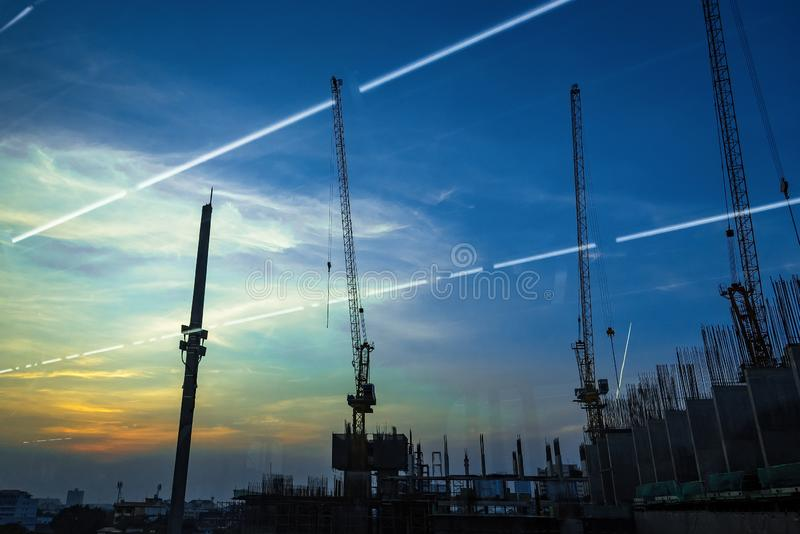 View of Industrial landscape with silhouettes of cranes on the sunset background From the windows of the electric train.Bangkok, stock photos
