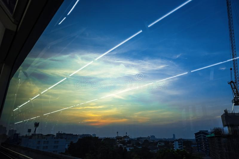 View of Industrial landscape with silhouettes of cranes on the sunset background From the windows of the electric train.Bangkok, royalty free stock photo