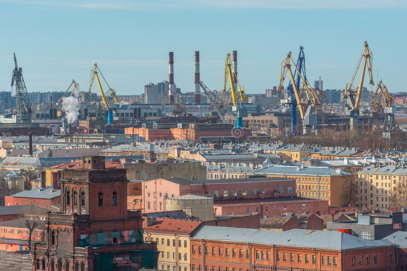 View of the industrial rafon of the city with factories and old industrial buildings, including the port and marine cargo cranes royalty free stock photography
