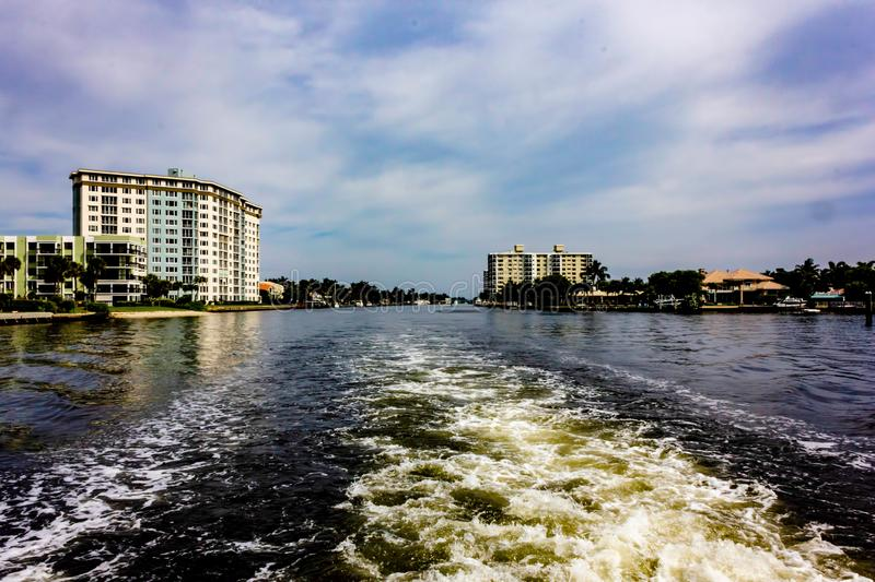 A View From the Inland Waterway in Delray Beach Florida. The wake from a yacht point the way up the inland waterway in Delray Beach Florida with clouds and blue royalty free stock photography