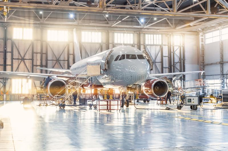 View inside the aviation hangar, the airplane mechanic working around the service.  royalty free stock images