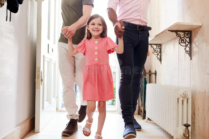 View Inside Hallway As Same Sex Male Couple With Daughter Open Front Door Of Home stock photos