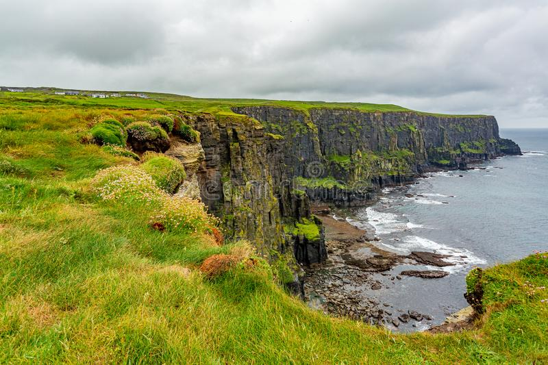View of the Irish countryside and rocky cliffs along the coastal walk route from Doolin to the Cliffs of Moher. Geosites and geopark, Wild Atlantic Way, rainy royalty free stock photo