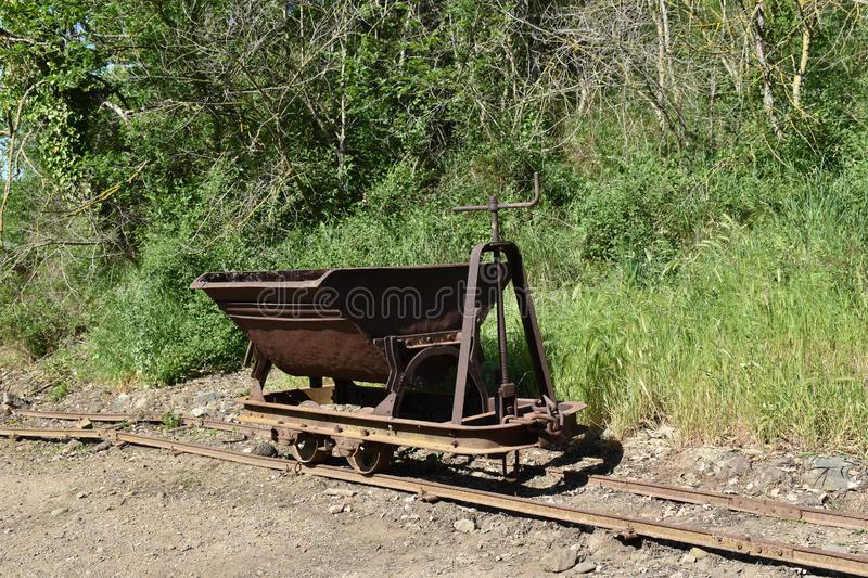 View of iron mine cart on rails. Brown storic green plants stock photos