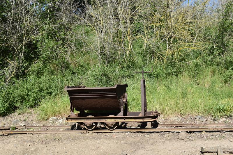 View of iron mine cart on rails. Brown outdoors nature green leaf grass stock photography