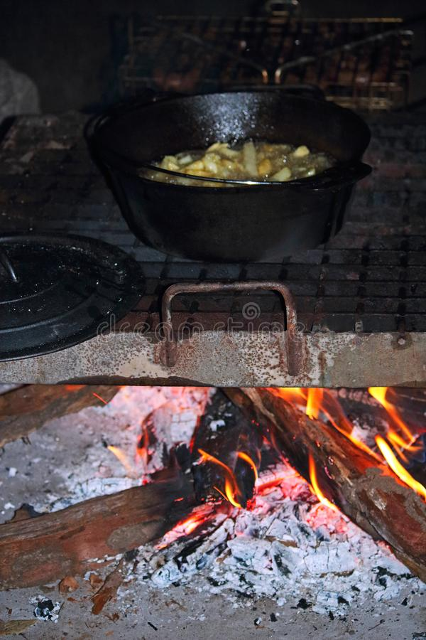 OPEN FIRE COOKING IN AN IRON POT. View of an iron pot on a grid with cut potato chips and oil cooking on an open fire stock photography